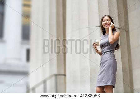 Lawyer businesswoman professional walking outdoors talking on cell smart phone drinking coffee from disposable paper cup. Multiracial Asian / Caucasian businesswoman smiling