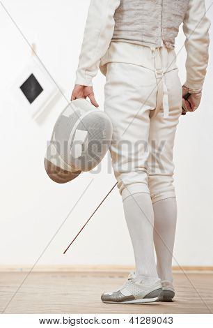 fencer in protective sport wear with mask and rapier foil at training