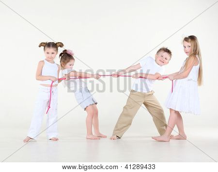 Four happy and cute little children in white pull pink rope.