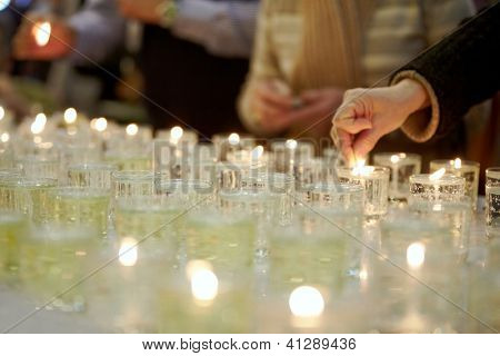 Hands lighting funeral candles