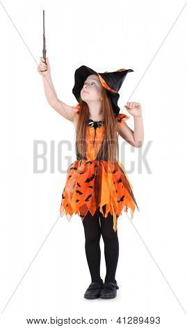 Little girl in orange costume of witch for Halloween holds up and looks at wand isolated on white background.