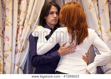 Dark-haired young man embrace young red-haired woman near curtained window.