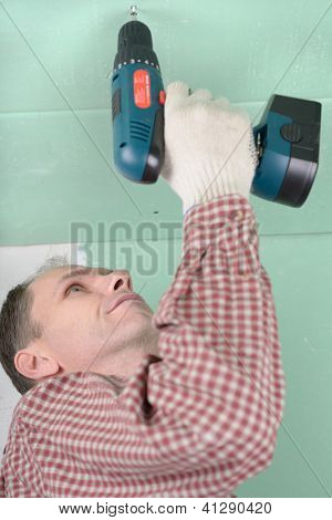 Man installing drywall using cordless drill