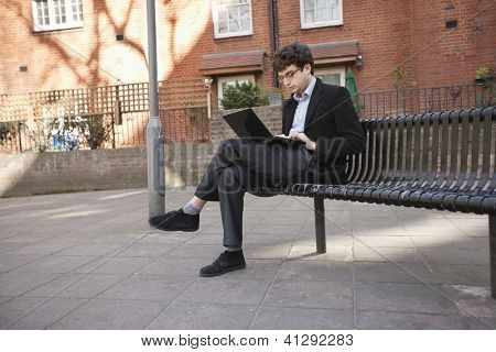 Young businessman using laptop while sitting on bench