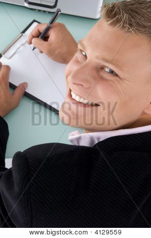 Back Pose Of Smiling Employee With Pen And Writing Board
