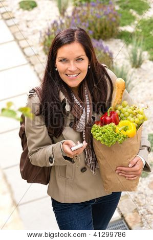 Happy woman shopping phone groceries texting vegetables mobile bag
