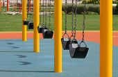 A row of swings in a park near a sea side at Bahrain