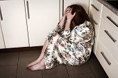 stock photo of loneliness  - Adult woman crying sitting on the floor - JPG