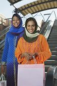 image of dupatta  - Portrait of two Indian friends standing with shopping bags with escalators in the background - JPG