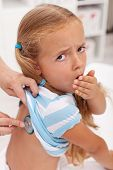 Coughing little girl at the doctors being checked with stethoscope