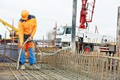 stock photo of formwork  - builder worker with vibrator machine compacting poured concrete into reinforcement formwork - JPG