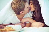 stock photo of flirtatious  - Young amorous couple kissing under blanket - JPG