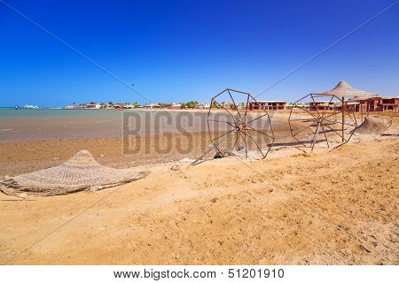 Devastated beach with broken parasols at Red Sea in Egypt