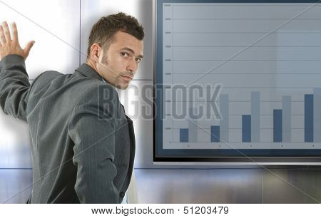 Young businessman doing presentation at meetingroom standing front of big LCD display, presenting charts.