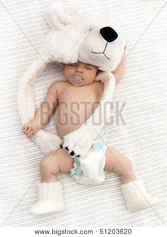 Lovely newborn baby sleeping with dummy, wearing big bear hat and knitted boots.