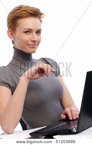 Smiling young businesswoman working on laptop computer.