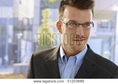 Closeup portrait of young businessman in glasses standing outdoors.