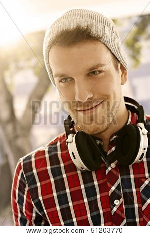 Closeup portrait of trendy young man smiling outdoors, wearing cap.