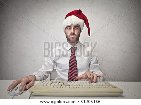businessman with Santa hat working on the computer