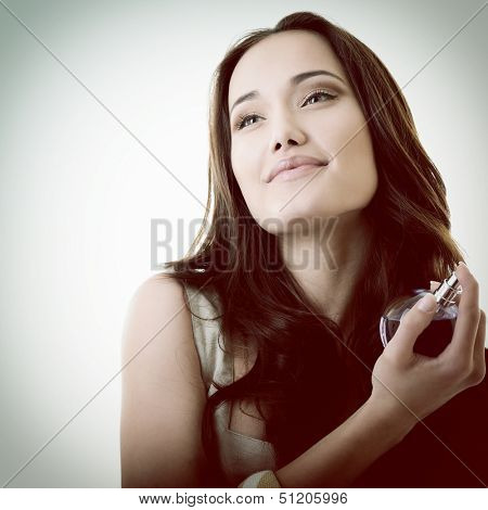 Woman with perfume, young beautiful girl holding bottle of perfume and smelling aroma, toned