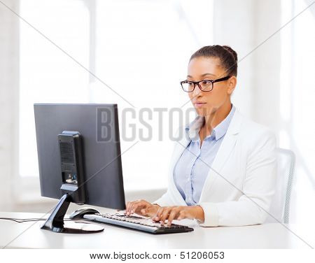 business and internet concept - african businesswoman with computer in office