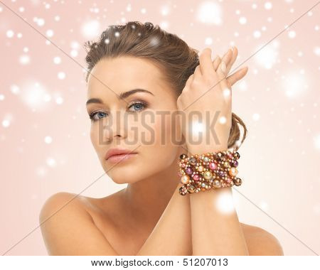 jewelry, luxury, bridal concept - beautiful woman wearing hand jewelry with beads