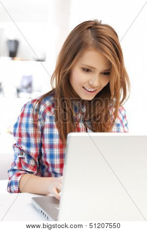 education and internet concept - smiling student girl with laptop at school