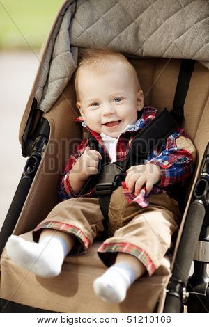 Cute little smiling baby in a baby carriage on the streets of the city. Smile of a  child sitting in a pram. A child laughs