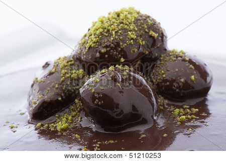 Close up of flowing down chocolate on profiterole