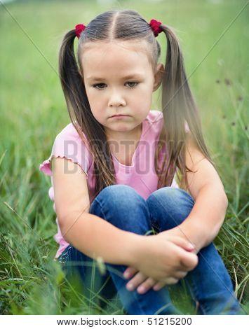 Sad little girl is sitting on green grass, outdoor shoot