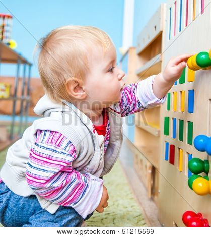little boy in the classroom early development plays with numerous bright toys