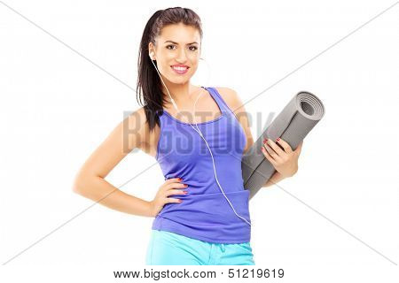 Female athlete listening music and holding a mat, isolated against white background