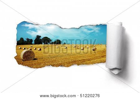 Tearing a paper frame hole to reveal hay bale field landscape