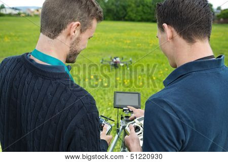 Rear view of young engineers with remote controls and screen operating UAV helicopter in park