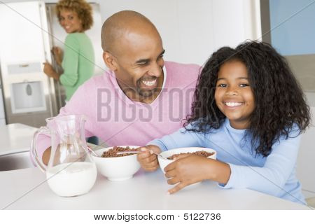 Father Sitting With Daughter As She They Eat Breakfast With Her Mother In The Background