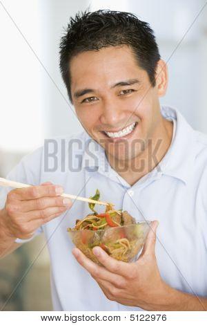 Man Enjoying Chinese Food With Chopsticks