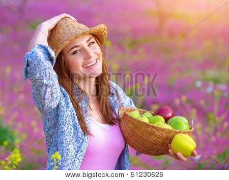 Closeup portrait of pretty woman with apples basket, having picnic on pink floral meadow, harvest season, gardening concept