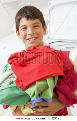 Young Boy Holding A Pile Of Laundry