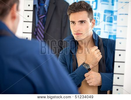young man preparing for work, dressing up and looking himself in mirror