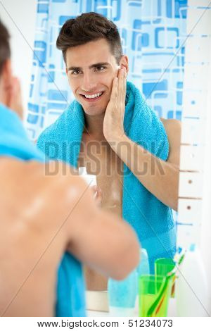 Young handsome man applying aftershave, skincare