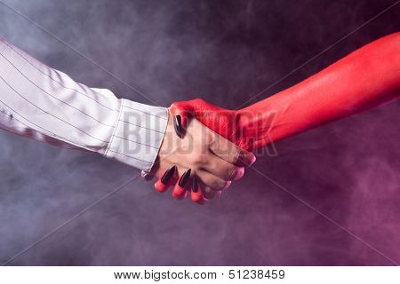 Businessman making a deal with devil, studio shot on smoky background
