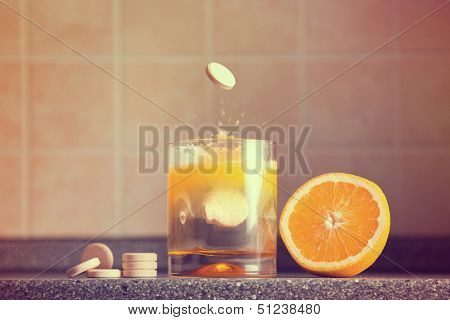 Artistic shot of vitamin C family, orange, tablet stack, dissolving tablet