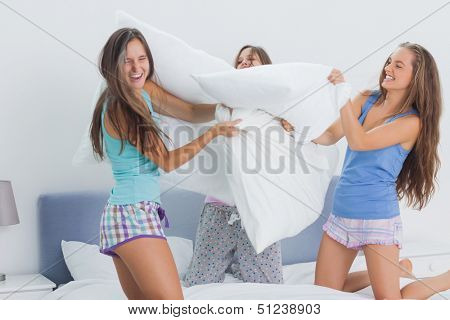 Friends having pillow fight at home at slumber party