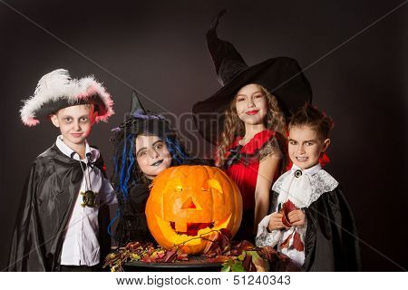 Cheerful children in halloween costumes posing with pumpkin. Over dark background.