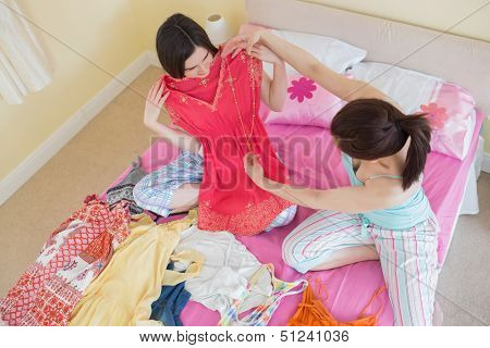 Cute girls looking at a dress at a sleepover at home in bedroom