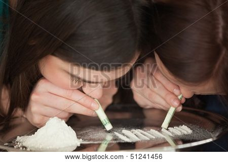 Two young girls snorting an illegal white powder with rolled up dollar bills