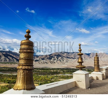 Dhvaja (victory banners), on the roof of Thiksey gompa (Tibetan BUddhistm monastery) and view of Indus valley. Ladakh, India