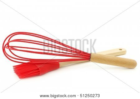 silicon egg beater and spatula with wooden handle on a white background