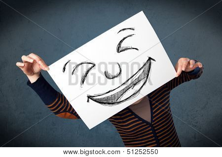 Young woman holding a paper with a drawed smiley face on it in front of her head