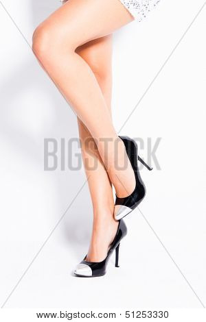 woman legs in elegant black and silver high heel shoes studio shot